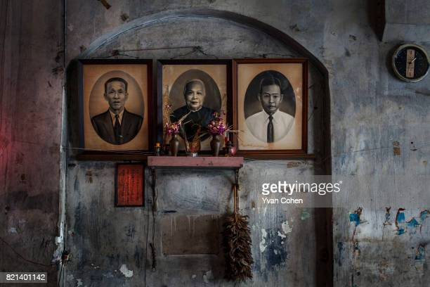 Chinese ancestor shrine decorated with black and white pictures of deceased family members in a car workshop in Bangkok The Thai capital Bangkok is...