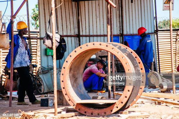 Chinese and African workers pause at the construction site for a hydro pumping station which will supply water from the Limpopo river to nearby rice...