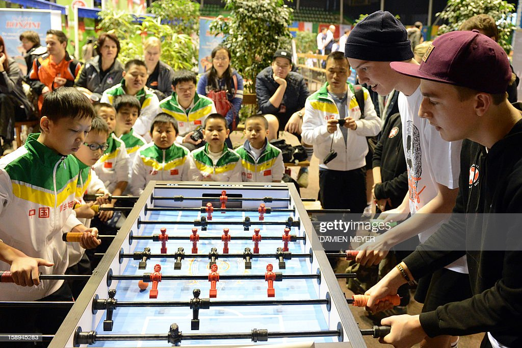 Chinese (L) and Danish (R) competitors take part in the ITSF 2013 table soccer (aka babyfoot) World Cup on January 4, 2013 in Nantes, western France.