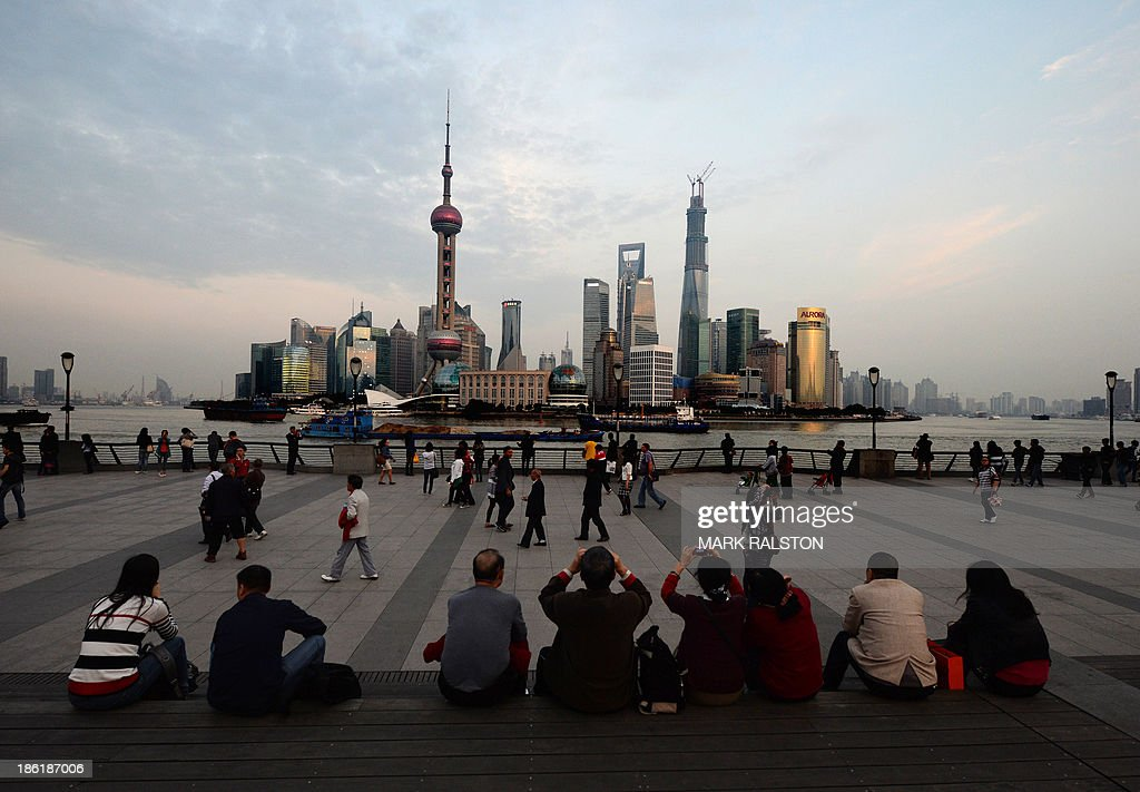 Chinese and foreign tourists view the Pudong financial district skyline from the historic Bund in Shanghai on October 29 2013 China's ruling...