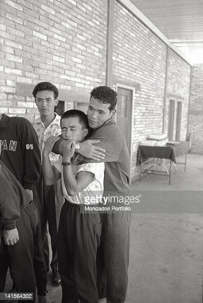 Chinese and Japanese athletes hugging during Rome Olympics Rome 1960