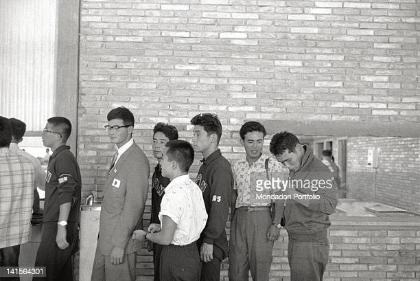 Chinese and Japanese athletes talking in a queue during Rome Olympics Rome 1960