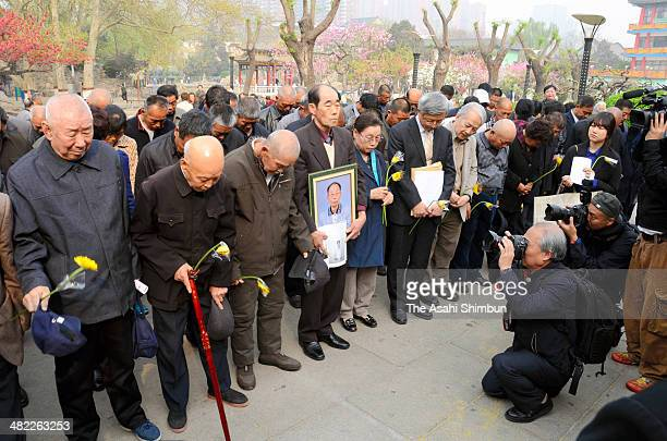 Chinese and South Koreans offer a prayer during a memorial ceremony for the victims of wartime forced labour in Japan on April 2 2014 in Shijiazhuang...