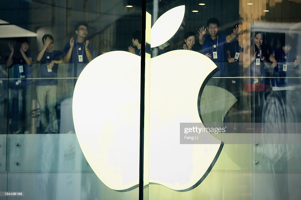 Chinese Apple staff members cheer in the new Apple Store before it opens in Wangfujing shopping district on October 20, 2012 in Beijing, China. Apple Inc. opened its sixth retail store on the Chinese mainland Saturday. The new Wangfujing store is Apple's largest retail store in Asia.