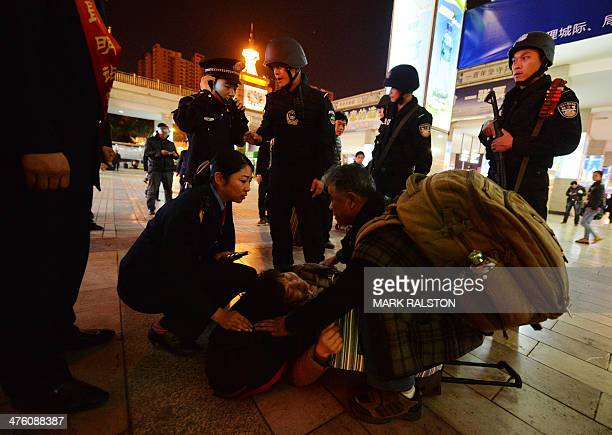 Chinese armed police and officials help a sick woman at the scene of the terror attack at the main train station in Kunming Yunnan Province on March...