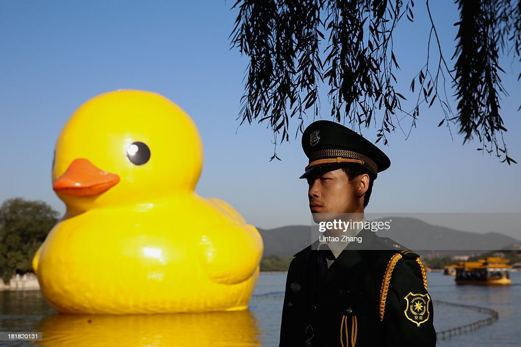 A chinese armed policeman stands on duty in front of the big yellow duck at the Summer Palace Kunming Lake on September 26, 2013 in Beijing, China. After touring 13 cities in 10 countries, the giant rubber duck designed by Dutch artist Florentijn Hofman will be in at Summer Palace from September 26 to October 26.