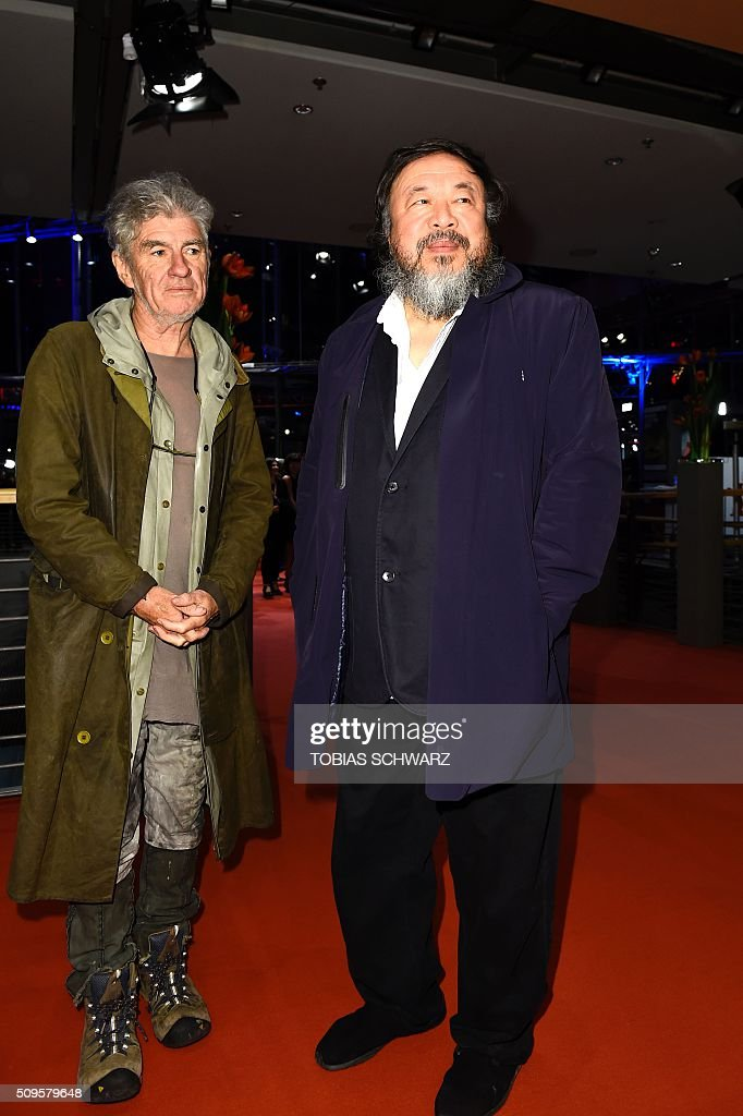 Chinese artist Ai Weiwei (R) and cameraman Christopher Doyle pose upon arrival for the film 'Hail, Caesar!' screening as opening film of the 66th Berlinale Film Festival in Berlin on February 11, 2016. / AFP / TOBIAS SCHWARZ