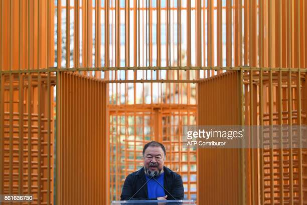 Chinese Artist Ai Weiwei delivers a speech as attends his art installation exploring migration entitled 'Good Fences Make Good Neighbors' during a...