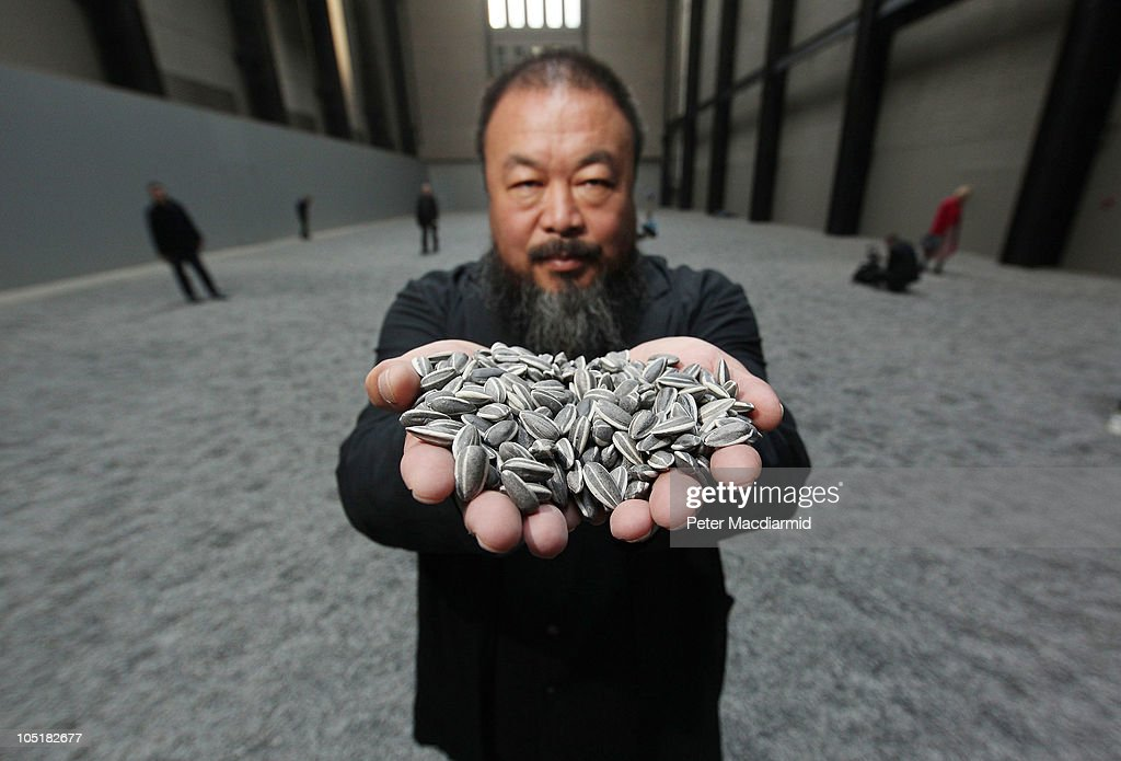 Chinese Artist <a gi-track='captionPersonalityLinkClicked' href=/galleries/search?phrase=Ai+Weiwei&family=editorial&specificpeople=4331218 ng-click='$event.stopPropagation()'>Ai Weiwei</a> holds some seeds from his Unilever Installation 'Sunflower Seeds' at The Tate Modern on October 11, 2010 in London, England. The sculptural installation comprises 100 million handmade porcelain replica sunflower seeds. Visitors to the Turbine Hall will be able to walk on the work - which opens on October 12, 2010 and runs until May 2, 2011.