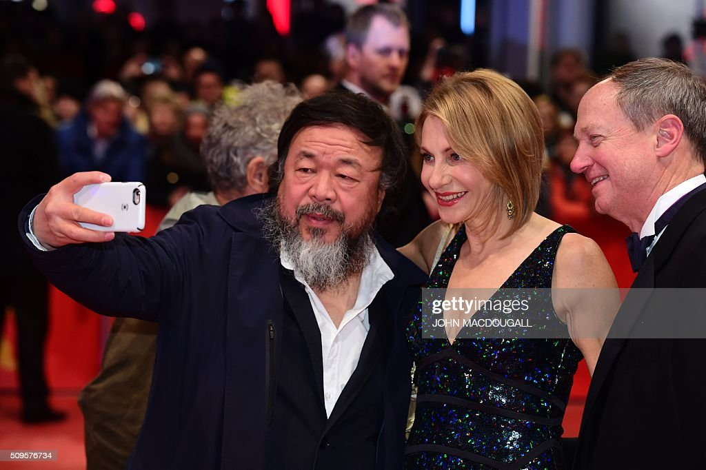 Chinese artist Ai Weiwei (L) makes a selfie photo with Ambassador to Germany John B Emerson and his family as they arrive on the red carpet for the film 'Hail, Caesar!' screening as opening film of the 66th Berlinale Film Festival in Berlin on February 11, 2016. Eighteen pictures will vie for the Golden Bear top prize at the event which runs from February 11 to 21, 2016. / AFP / John MACDOUGALL