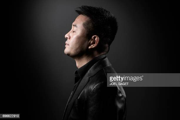 TOPSHOT Chinese artist Liu Bolin poses during a photo session in Paris on June 10 2017 / AFP PHOTO / JOEL SAGET