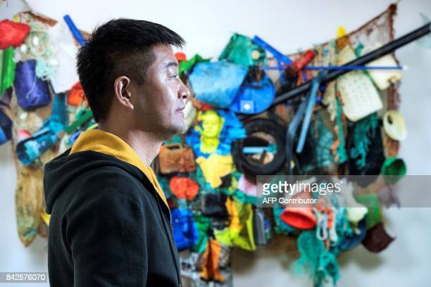 Chinese artist Liu Bolin poses in front of his artwork during the preview of his exhibition at the Beijing Paris gallery on September 4 2017 in Paris...