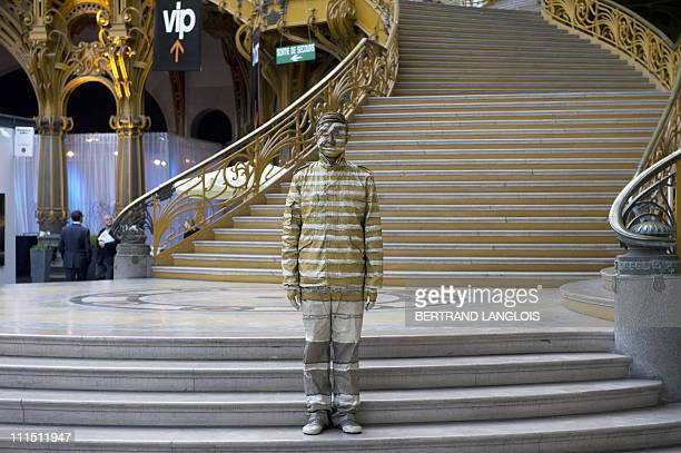 Chinese artist Liu Bolin stands at the end of a happening at the Grand Palais in Paris on April 1 2011 Bolin from Shandong China manages to...