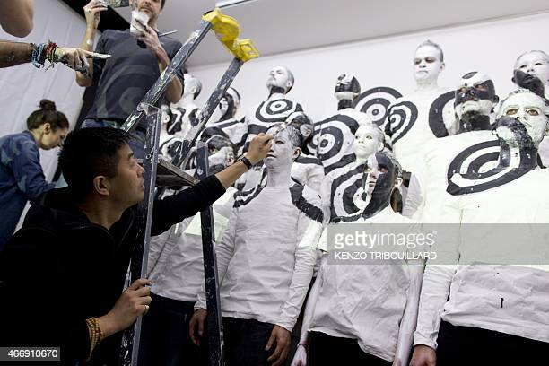 Chinese artist Liu Bolin takes part in a performance on March 19 2015 in Paris AFP PHOTO / KENZO TRIBOUILLARD == RESTRICTED TO EDITORIAL USE...