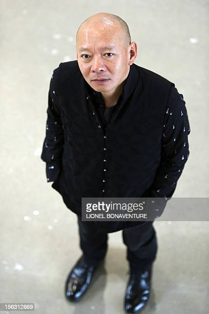 Chinese artist Yue Minjun poses as part of an exhibition devoted to his work and entitled 'L'ombre d'un fou rire' on November 13 2012 at the...