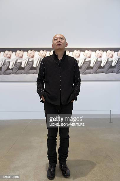 Chinese artist Yue Minjun poses in front of one of his painting displayed in an exhibition devoted to his work and entitled 'L'ombre d'un fou rire'...