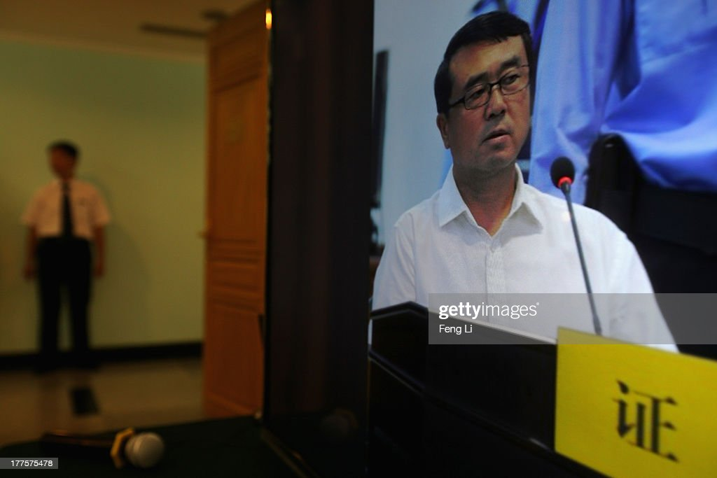 A Chinese attendant stands near a screen showing a picture of former police chief Wang Lijun as he gives evidence on the third day of the trial of disgraced politician Bo Xilai at the Jinan Intermediate People's Court on August 24, 2013 in Jinan, China. Ousted Chinese politician Bo Xilai is standing trial on charges of bribery, corruption and abuse of power for a third day. Bo Xilai made global headlines last year when his wife Gu Kailai was charged and convicted of murdering British businessman Neil Heywood.