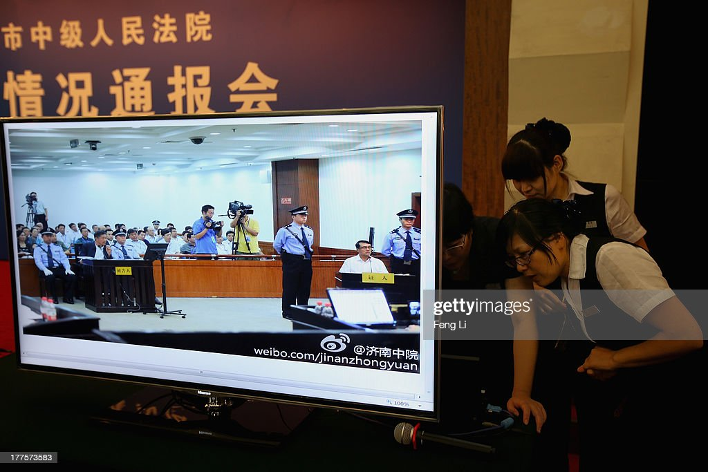 Chinese attendants looks the laptop behind a screen showing a picture of former police chief Wang Lijun (Right) as he gives evidence on the third day of the trial of disgraced politician Bo Xilai (Left) at the Jinan Intermediate People's Court on August 24, 2013 in Jinan, China. Ousted Chinese politician Bo Xilai is standing trial on charges of bribery, corruption and abuse of power for a third day. Bo Xilai made global headlines last year when his wife Gu Kailai was charged and convicted of murdering British businessman Neil Heywood.