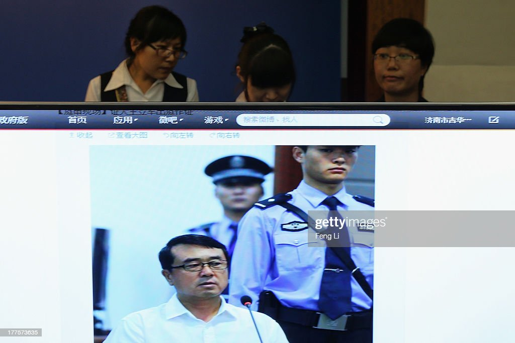 Chinese attendants stand behind a screen showing a picture of former police chief Wang Lijun as he gives evidence on the third day of the trial of disgraced politician Bo Xilai at the Jinan Intermediate People's Court on August 24, 2013 in Jinan, China. Ousted Chinese politician Bo Xilai is standing trial on charges of bribery, corruption and abuse of power for a third day. Bo Xilai made global headlines last year when his wife Gu Kailai was charged and convicted of murdering British businessman Neil Heywood.
