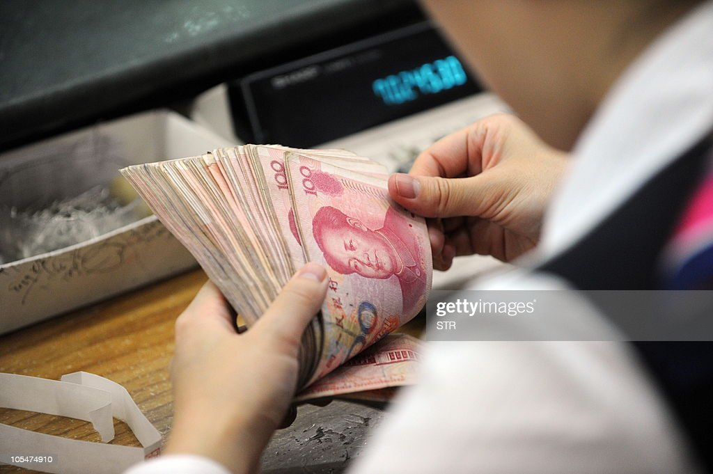 A Chinese bank clerk counts a stack of onehundred yuan notes for a customer at a bank in Hefei east China's Anhui province on October 14 2010 China...