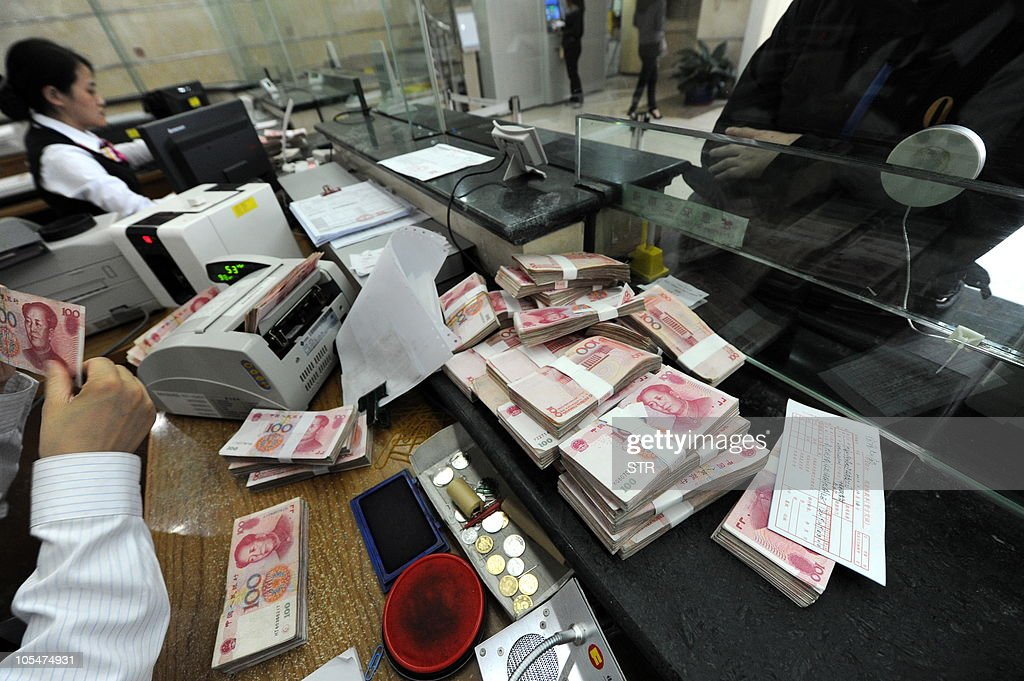 A Chinese bank clerk counts the stacks of onehundred yuan notes for a customer at a bank in Hefei east China's Anhui province on October 14 2010...