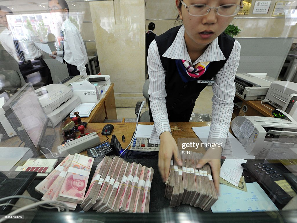 A Chinese bank clerk prepare to count the stacks of onehundred yuan notes for a customer at a bank in Hefei east China's Anhui province on October 14...