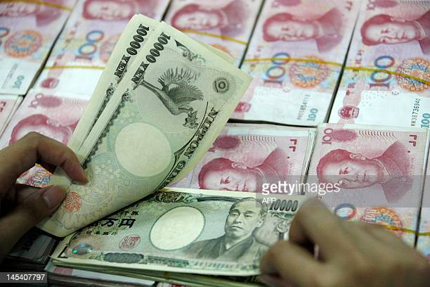 A Chinese bank clerk shows off 10000 Japanese Yen notes among the stacks of 100 yuan notes at a bank in Huaibei east China's Anhui province on May 29...