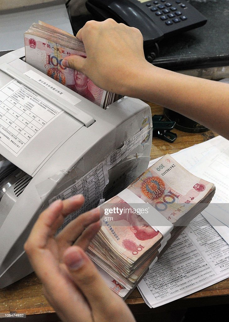 A Chinese bank clerk uses a machine to count the stacks of onehundred yuan notes for a customer at a bank in Hefei east China's Anhui province on...