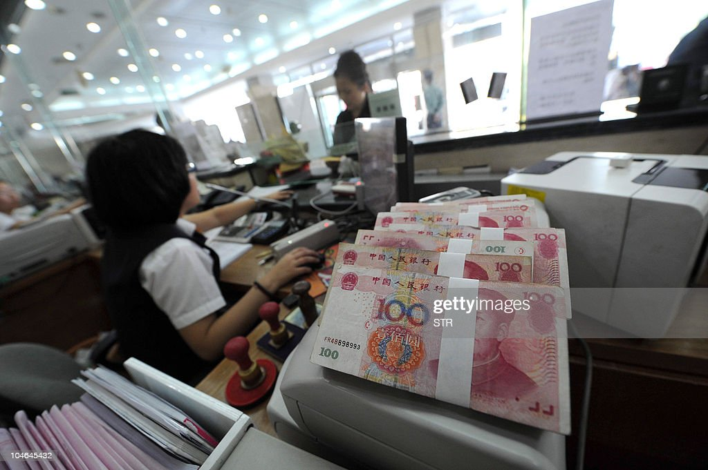 A Chinese bank worker attends to a customer with stacks of 100yuan notes at a bank counter in Hefei east China's Anhui province on September 30 2010...