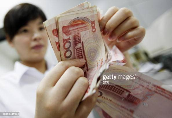 A Chinese bank worker counts stacks of 100 yuan notes at a bank in Huaibei in eastern China's Anhui province on August 4 2010 China must make the...