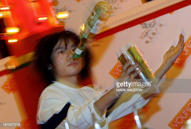 A Chinese barman shows his juggling skills during Christmas promotion at a shopping center in Shanghai 13 December 2006 China's economic boom and...
