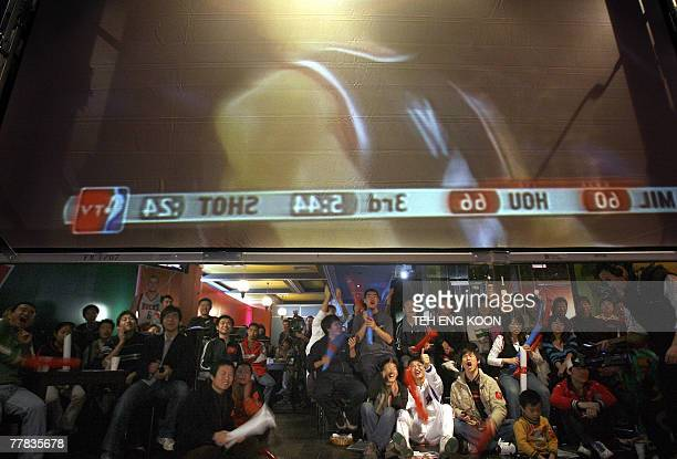 Chinese basketball fans watch a projector screen broadcasting a live NBA game between Houston Rockets and Milwaukee Bucks at a pub in Beijing 10...