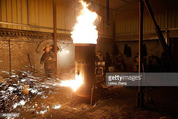Chinese blacksmiths man a furnace as they prepare to throw the molten metal against a cold stone wall to create sparks in Nuanquan Hebei Province on...