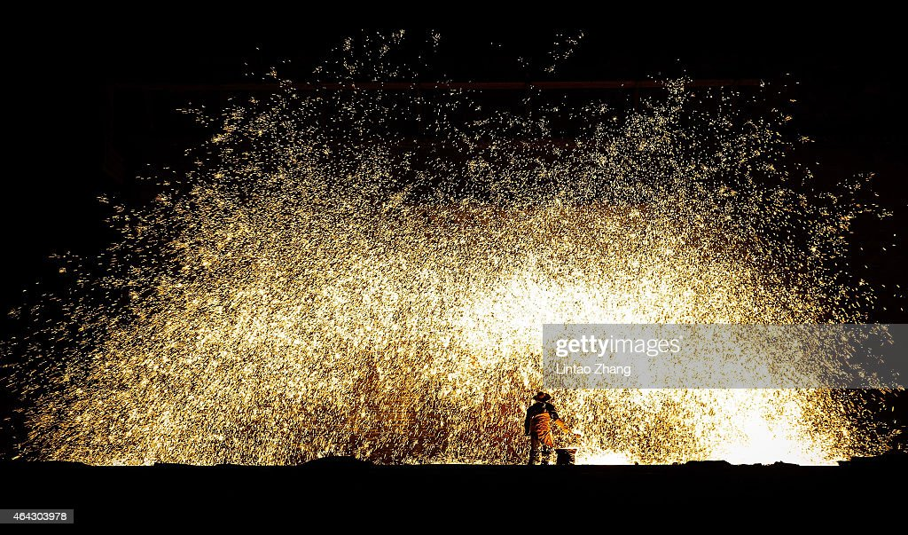 Chinese blacksmiths man a furnace as they prepare to throw the molten metal against a cold stone wall to create sparks on February 23 2015 in...
