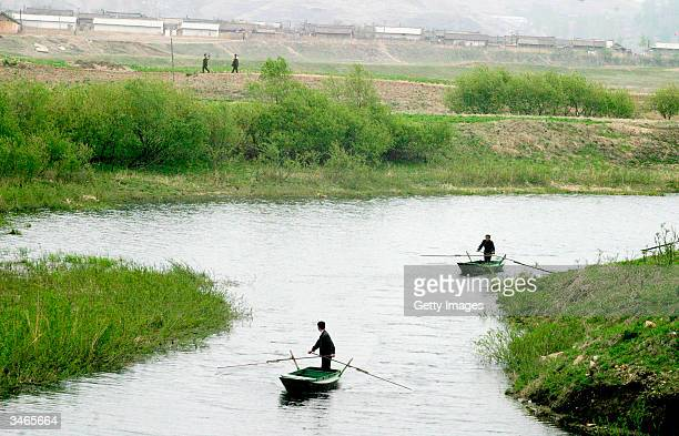 Chinese boatsmen return from a quick encounter with North Korean soldiers at a border crossing about 20 km north of the Ryochon disaster site April...