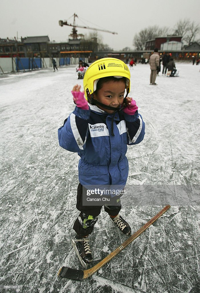 A Chinese boy adjusts his helmet whilst playing ice hockey on the frozen Shichahai Lake on January 3, 2006 in Beijing, China. Shichahai Lake is a popular place for winter sport and entertainment in Beijing.