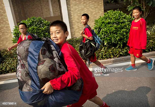 Chinese boy carries a bag of footballs as they head for training at the Evergrande International Football School on June 14 2014 near Qingyuan in...
