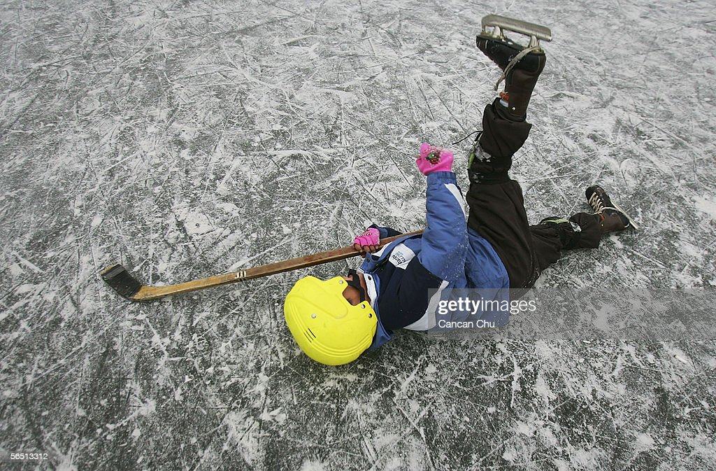 A Chinese boy falls down whilst playing ice hockey on the frozen Shichahai Lake on January 3, 2006 in Beijing, China. Shichahai Lake is a popular place for winter sport and entertainment in Beijing.