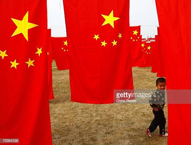 A Chinese boy hides behind China's national flag at Chaoyang park September 30 2006 in Beijing China Chinese people are preparing for National Day...