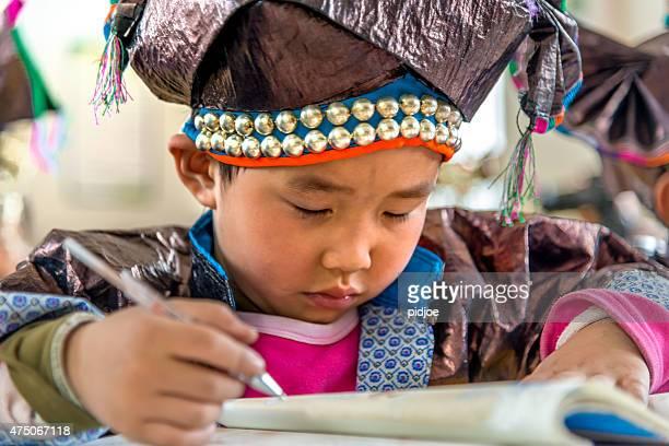 中国の伝統的な少年 Dong 衣類で働く学校