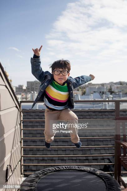 Chinese boy jumping on trampoline on rooftop