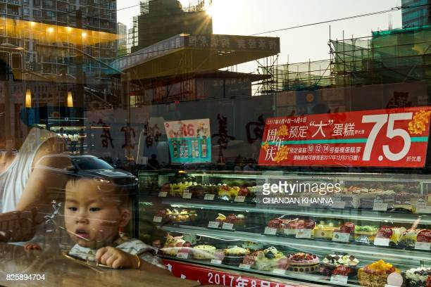 Chinese boy looks out from a pastry shop in Shanghai on August 3 2017 / AFP PHOTO / CHANDAN KHANNA