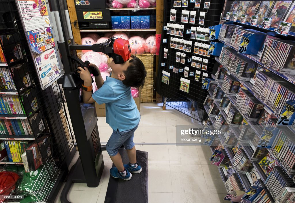 A Chinese boy tries out Nintendo Co.'s Virtual Boy console at the Super Potato video game store in the Akihabara district of Tokyo, Japan, on Tuesday, Aug. 8, 2017. Renewed interest in vintage Japanese videogamesis drawing buyers to the country'sonline markets and retro gaming shops. Photographer: Tomohiro Ohsumi/Bloomberg via Getty Images