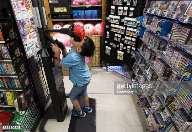 A Chinese boy tries out Nintendo Co's Virtual Boy console at the Super Potato video game store in the Akihabara district of Tokyo Japan on Tuesday...