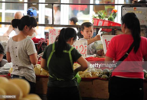 A Chinese boy whose migrant parents are unable to afford his kindergarden or preschool education in China's capital helps at his family's stall at a...