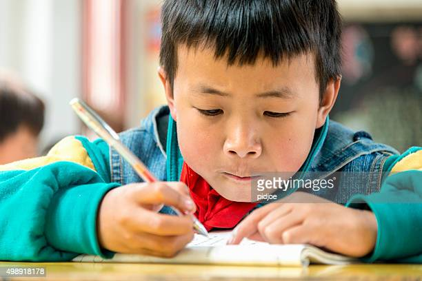 Chinese Boy working at school, highly concentrated