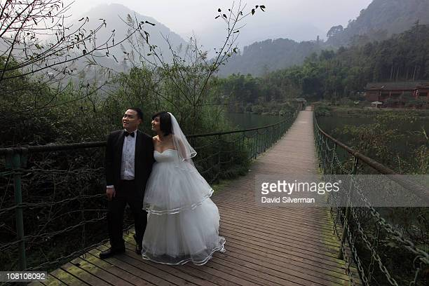 Chinese bride and groom pose for their wedding photos by one of the lakes December 1 2010 on Mount Emei in China's Sichuan province Mt Emei the...