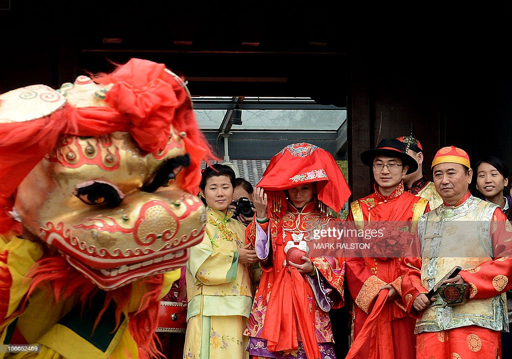 A Chinese bride (C) and groom watch a lion dance during their wedding at a temple beside Houhai Lake in Beijing on November 18, 2012. President Hu Jintao recently called for a new Chinese growth model, marked by greater domestic demand and private enterprise, to ensure the long-term health of the world's second largest economy. AFP PHOTO/Mark RALSTON