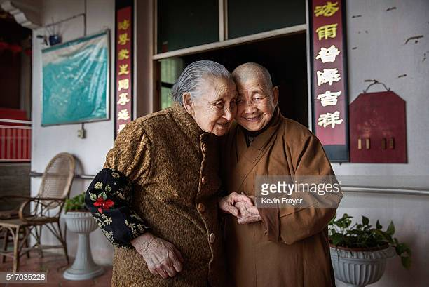 Chinese Buddhist nun Neng Qing who runs the facility and its one of its founders embraces an elderly Chinese resident as they greet each other at the...