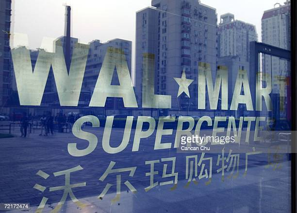 Chinese buildings are seen reflected on a window at Beijing's first WalMart supercenter October 14 2006 in Beijing China WalMart workers in China...